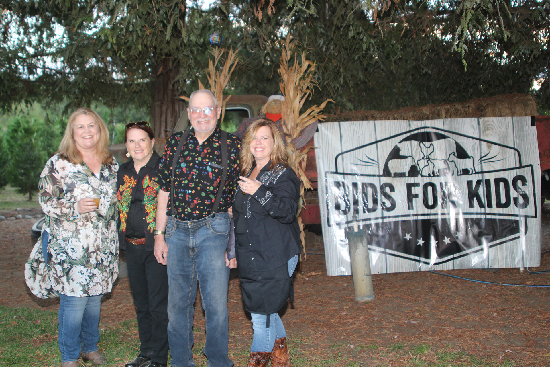 Group of people posing next to a bids for kids sign
