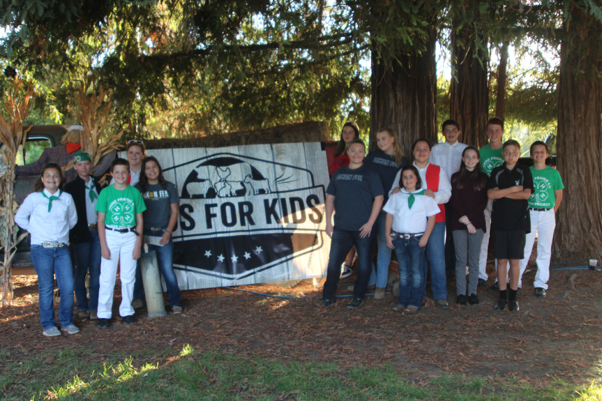 Solano County junior livestock exhibitors in front of Bids for Kids sign